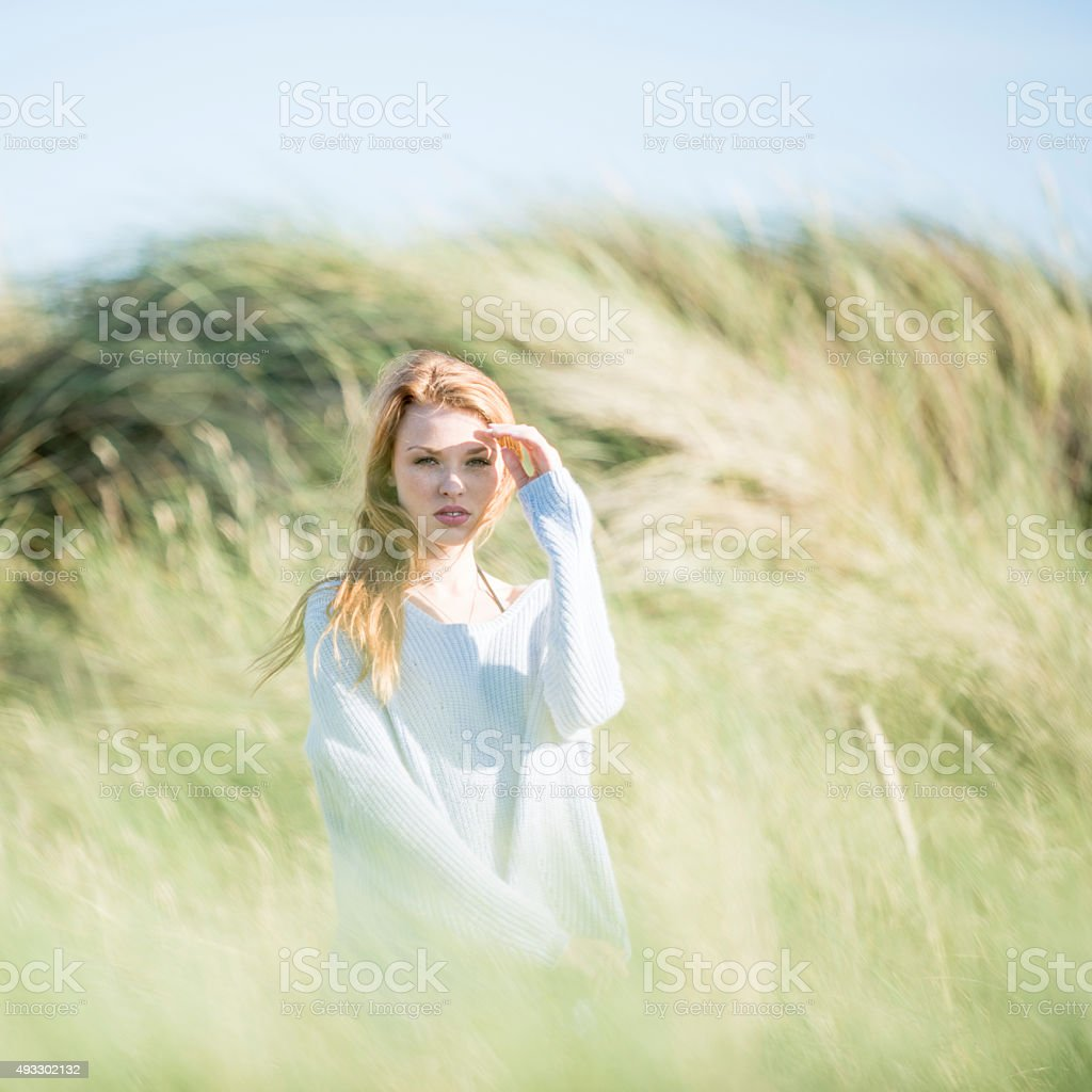 Beautiful young woman redhead in marram grass stock photo