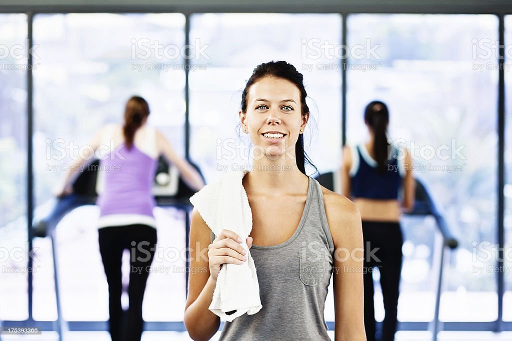 Beautiful young woman relaxes smiling after exercise in gym stock photo