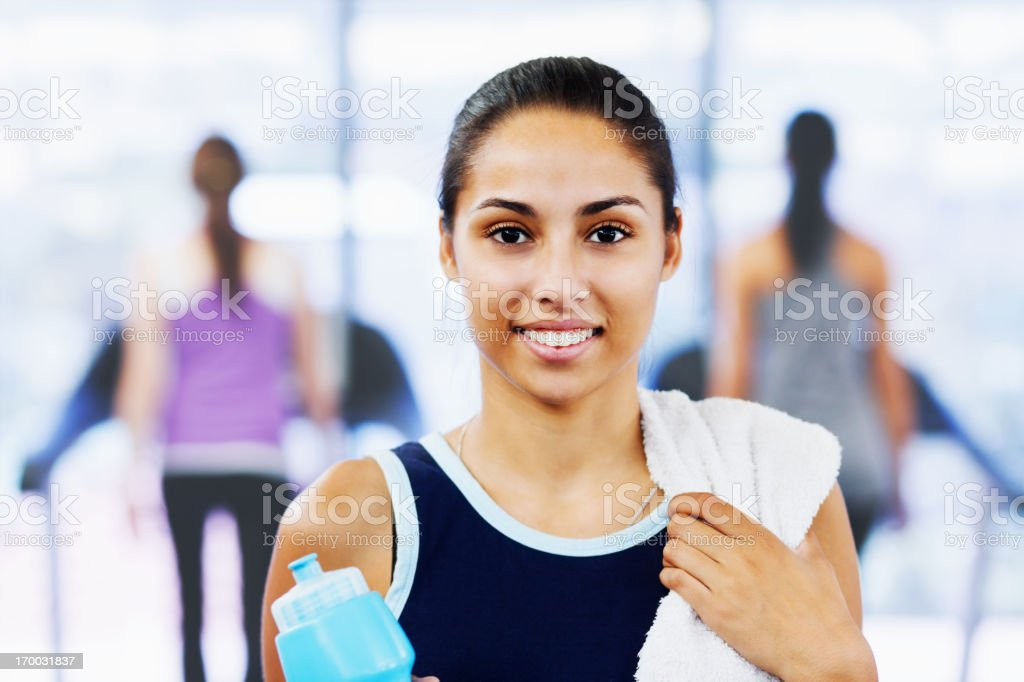 Beautiful young woman relaxing after exercising holding water and towel stock photo