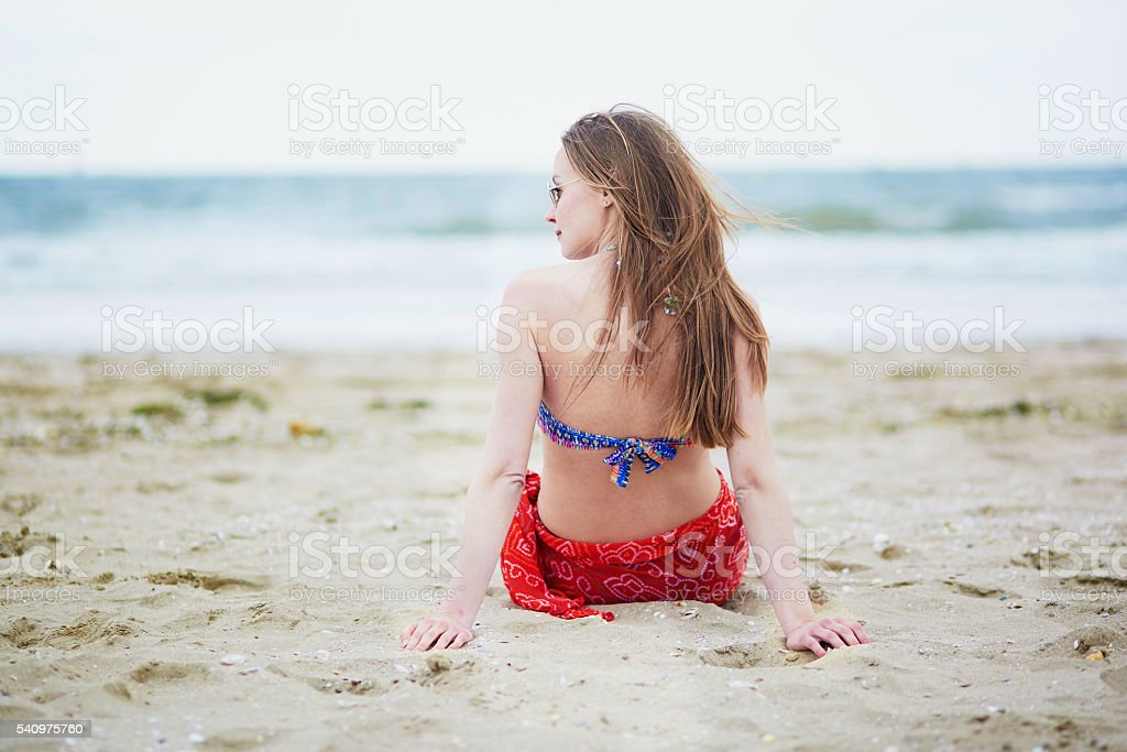 Beautiful young woman relaxing and sunbathing on beach stock photo