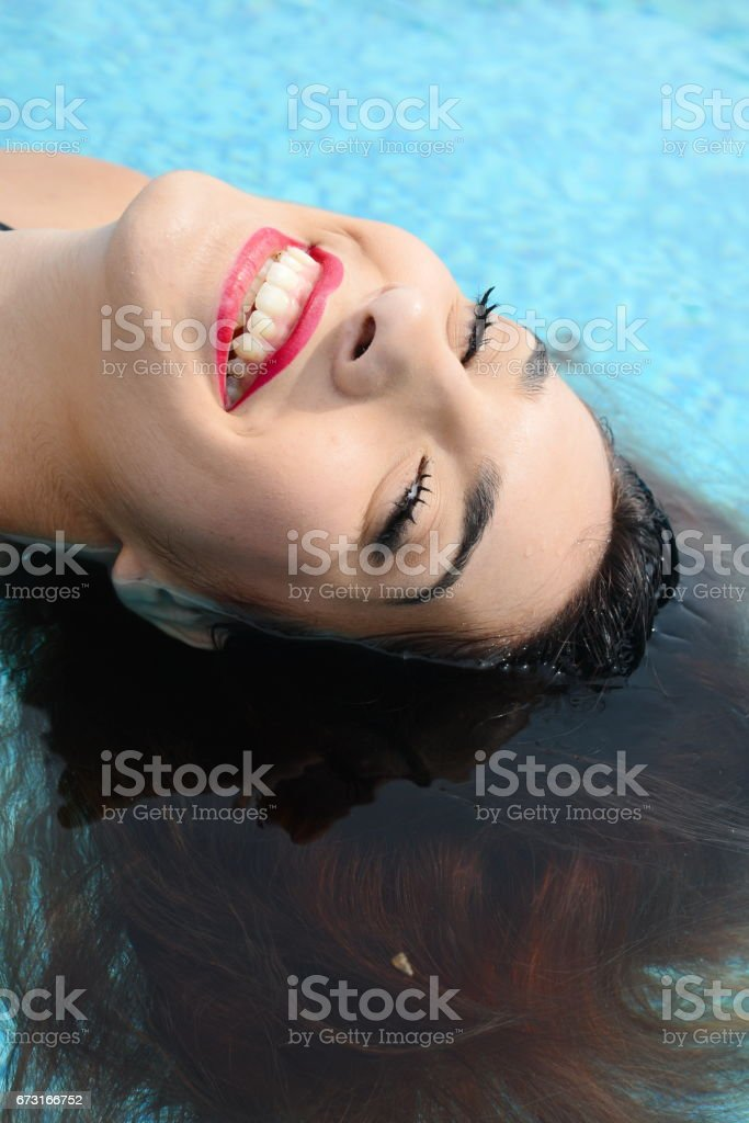 beautiful young woman relaxing in water by the swimming pool stock photo