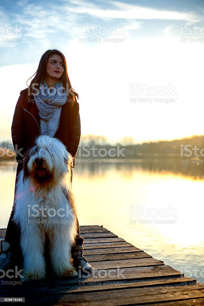 Beautiful young woman relaxing with her dog stock photo