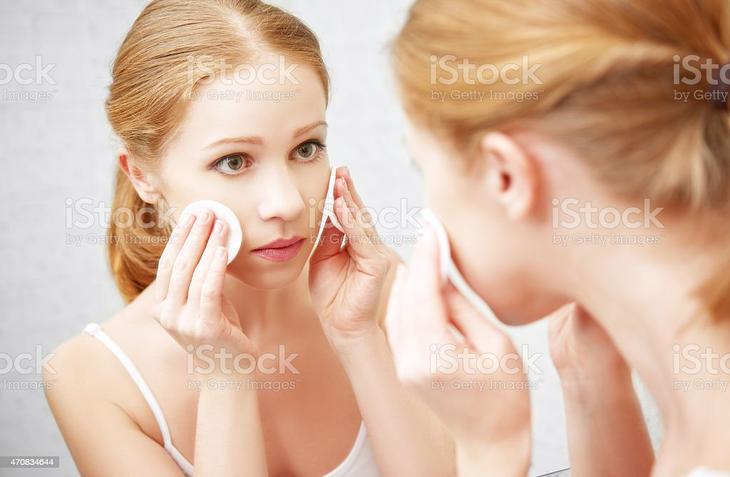 beautiful young woman removes makeup with face skin in mirror stock photo