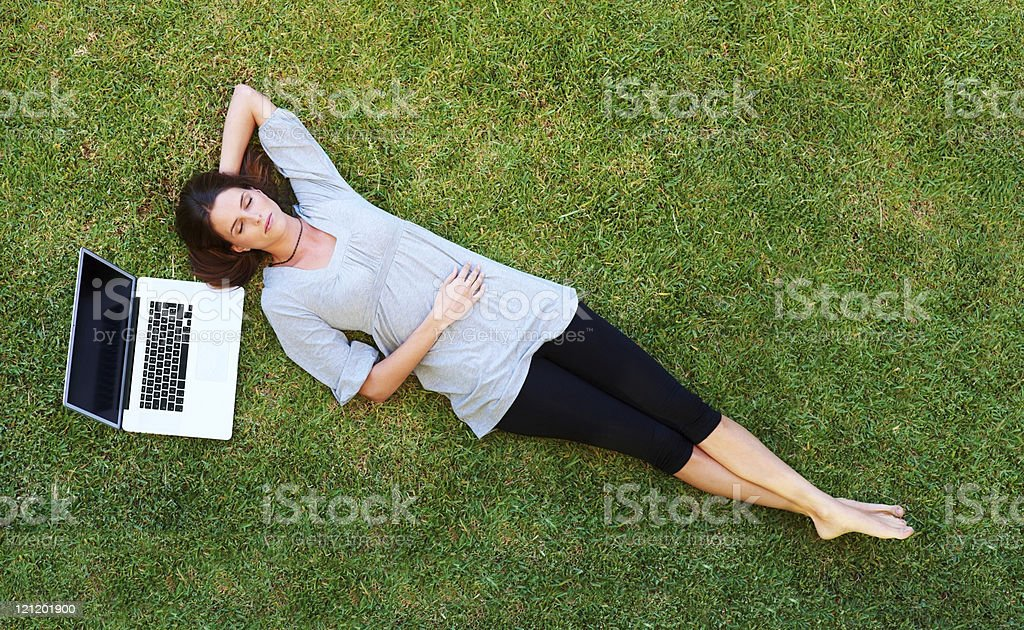 Beautiful young woman resting on grass with laptop stock photo