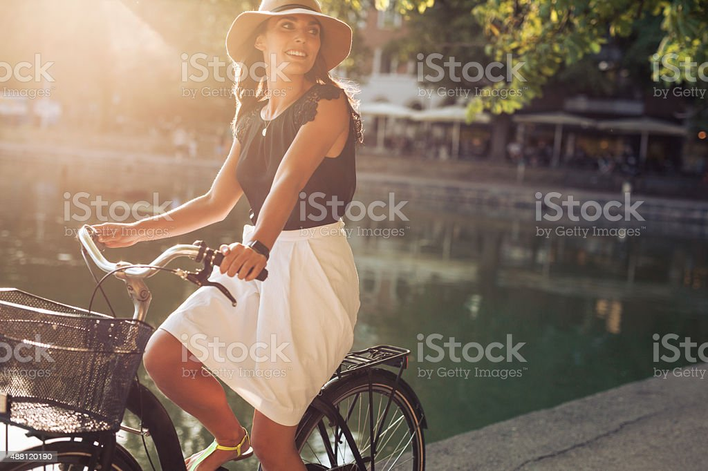 Beautiful young woman riding a bicycle stock photo