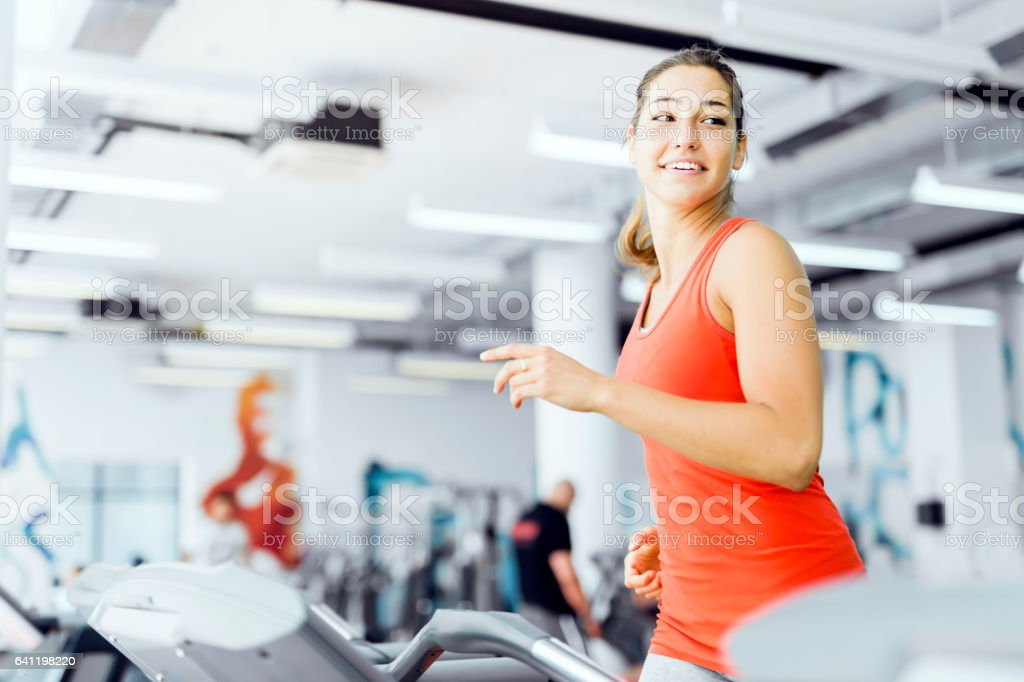 Beautiful young woman running on a treadmill in gym stock photo