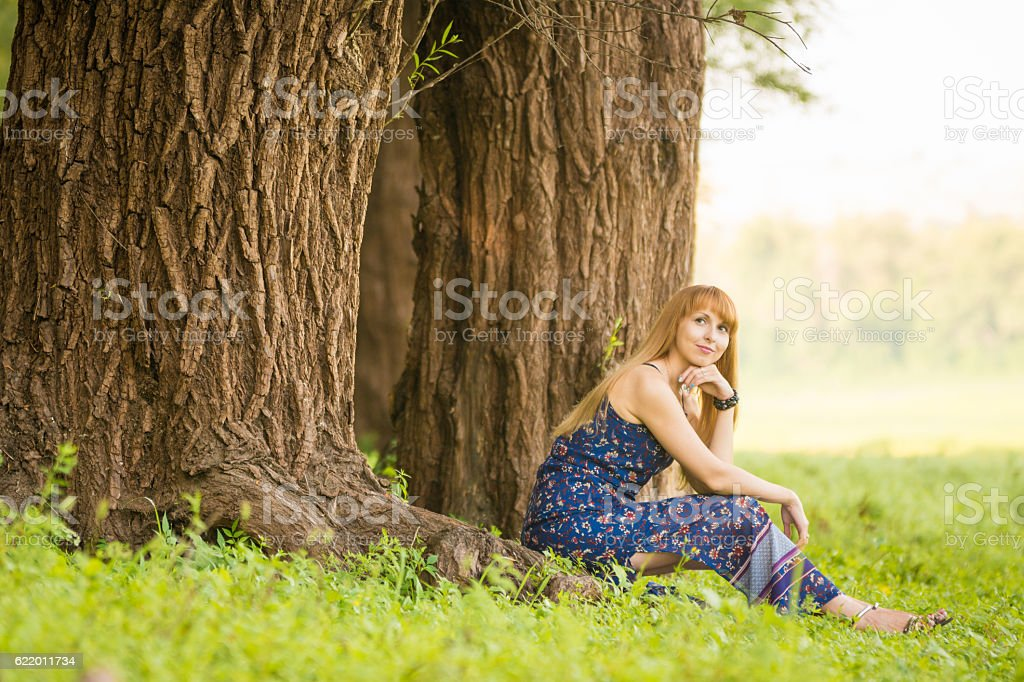 Beautiful young woman sat on roots of old large tree stock photo