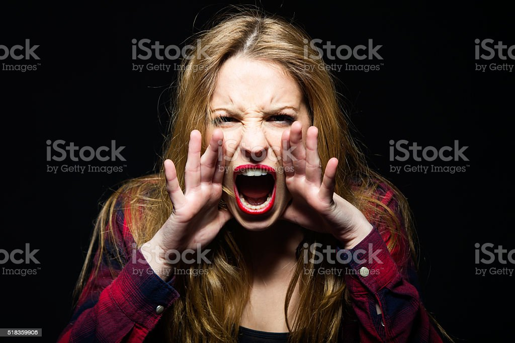 Beautiful young woman screaming. Isolated. stock photo