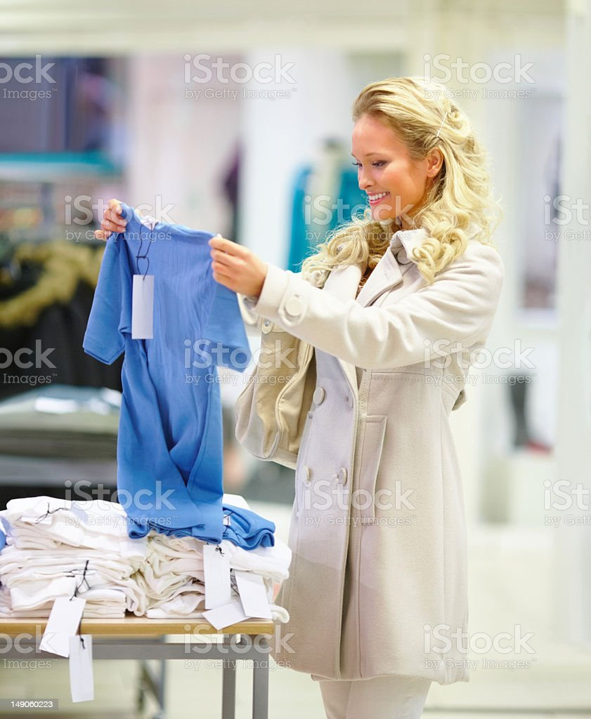 Beautiful young woman selecting clothes in mall royalty-free stock photo
