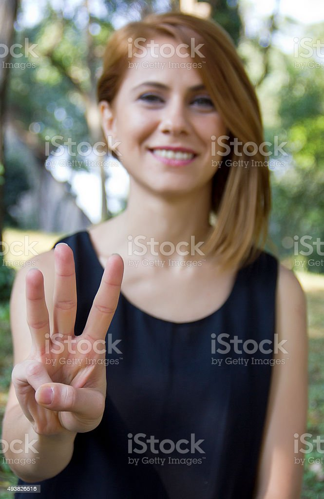 Beautiful young woman shows the number stock photo