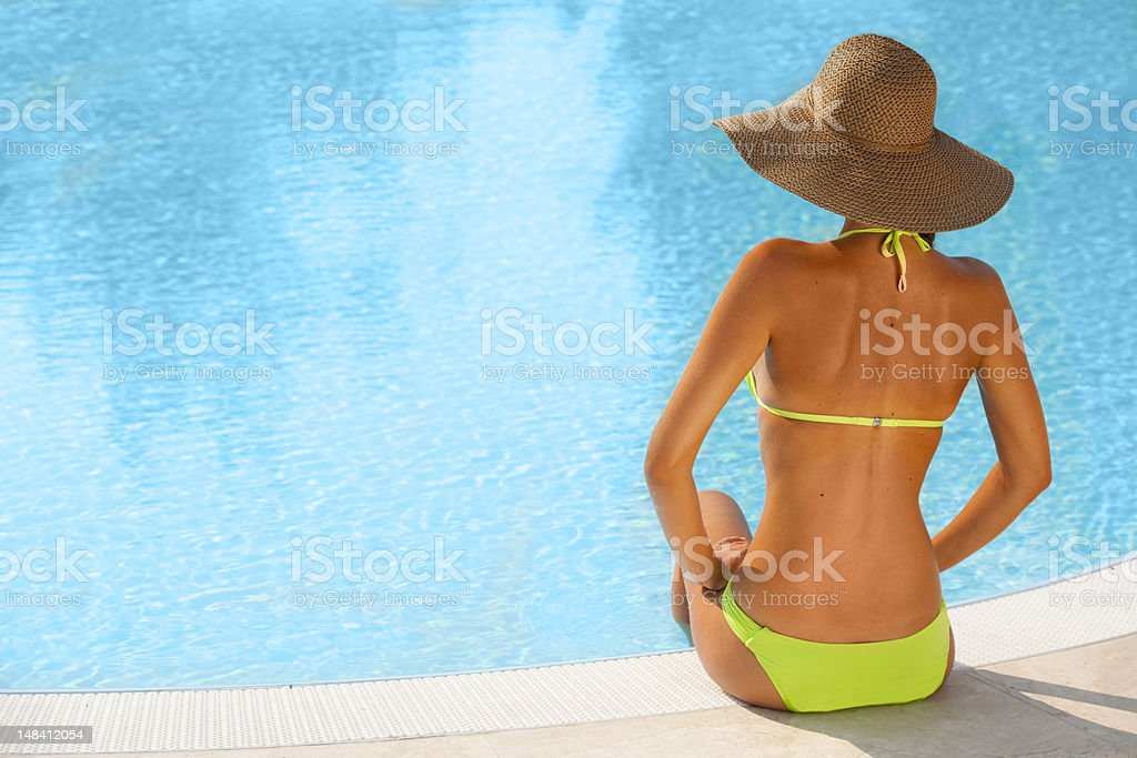 Beautiful Young Woman Sitting By Swimming-pool royalty-free stock photo