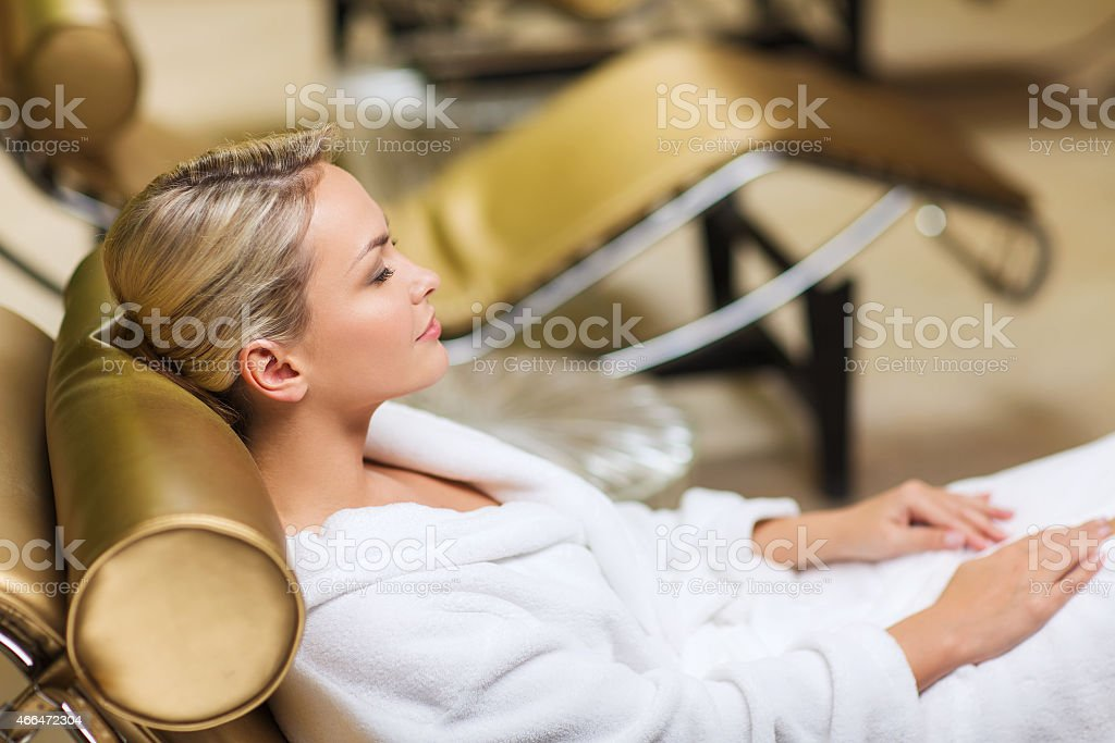 beautiful young woman sitting in bath robe at spa stock photo