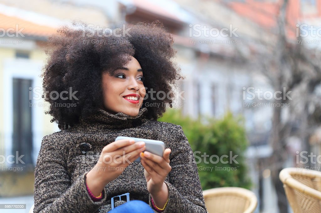 Beautiful young woman sitting in cafe and using smart phone stock photo
