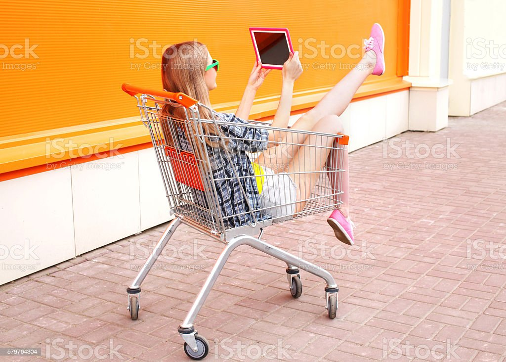 Beautiful young woman sitting in shopping trolley cart over colorful stock photo