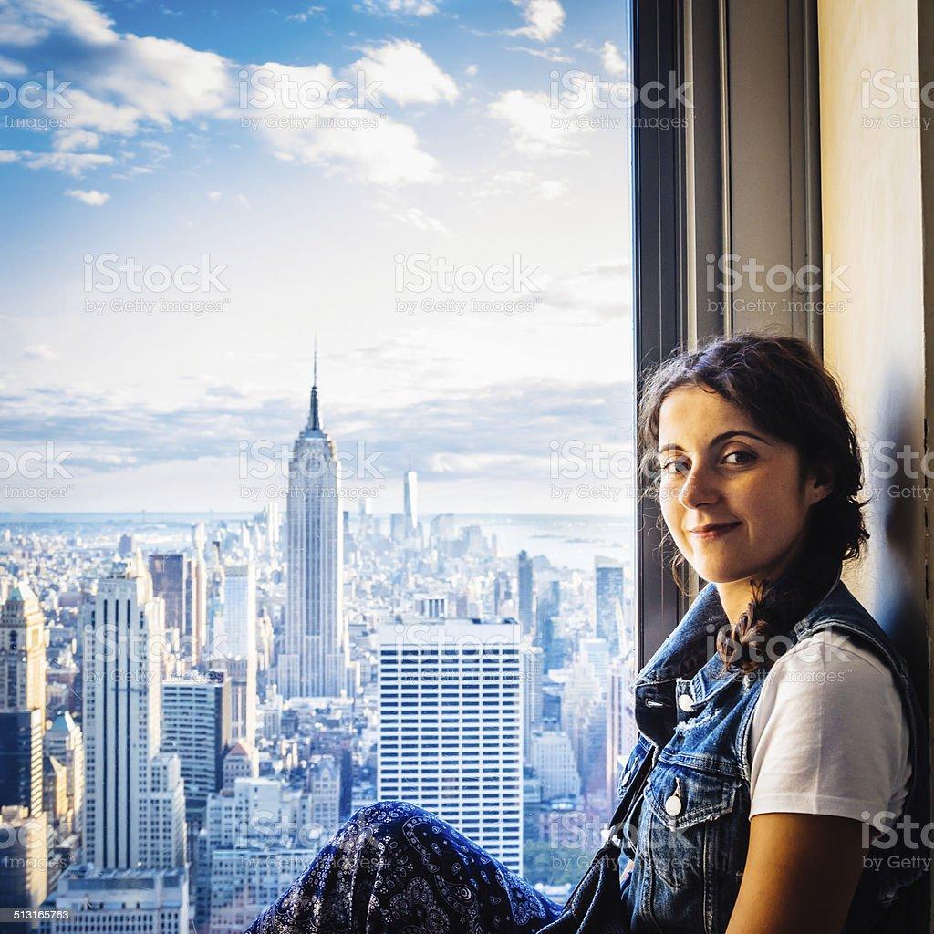Beautiful young woman sitting near a window in New York stock photo