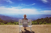 Beautiful young woman  sitting on a bench at Doi Inthanon
