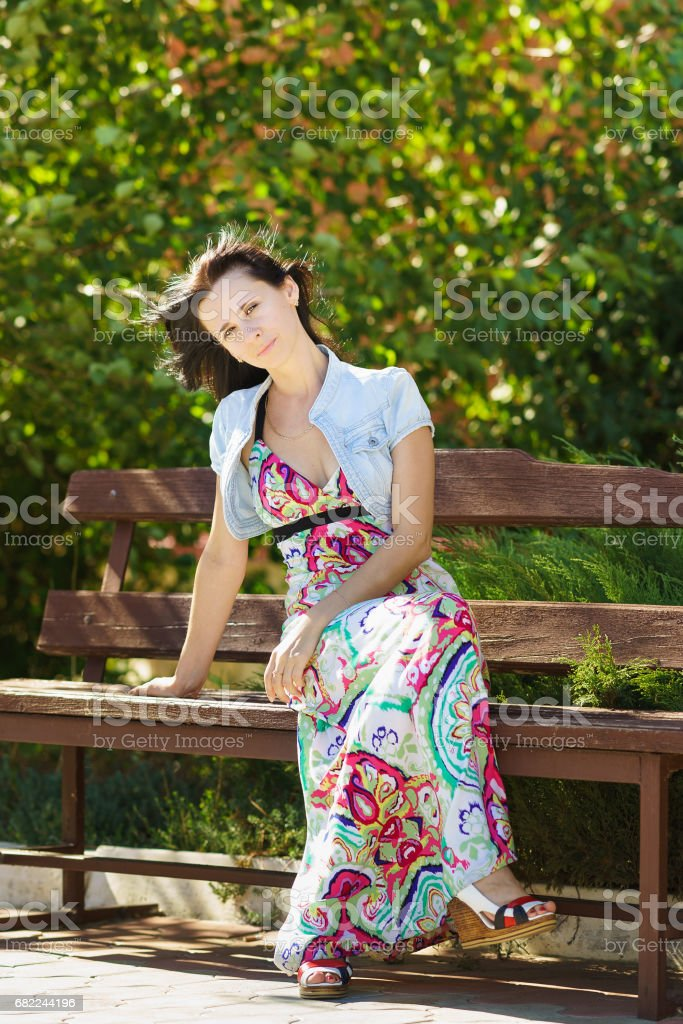 Beautiful young woman sitting on a bench in a city Park stock photo