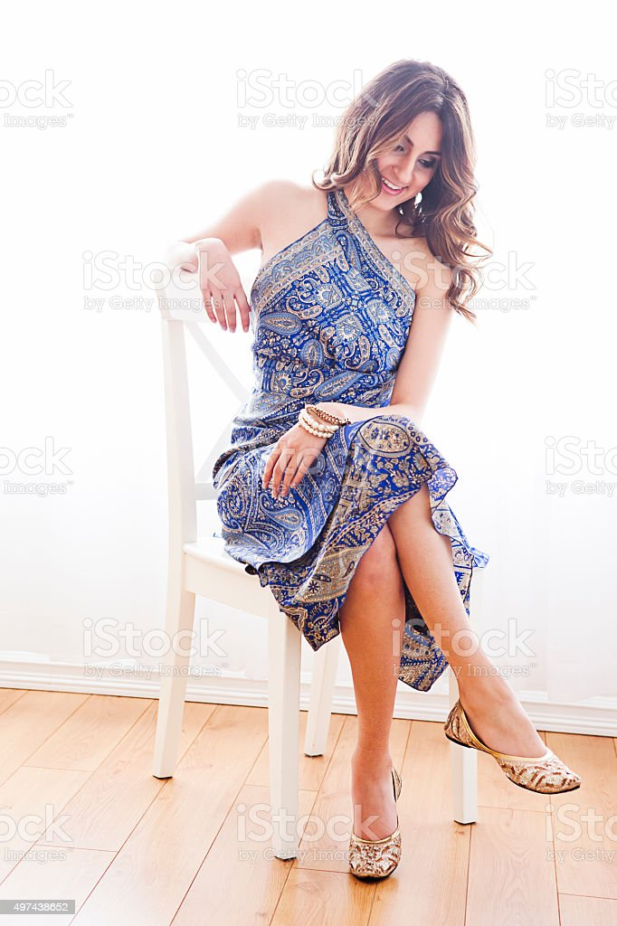 Beautiful young woman sitting on chair stock photo