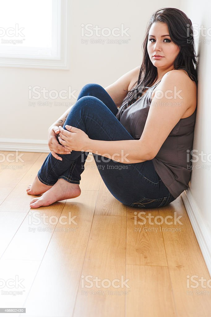 Beautiful young woman sitting on hardwood floor stock photo
