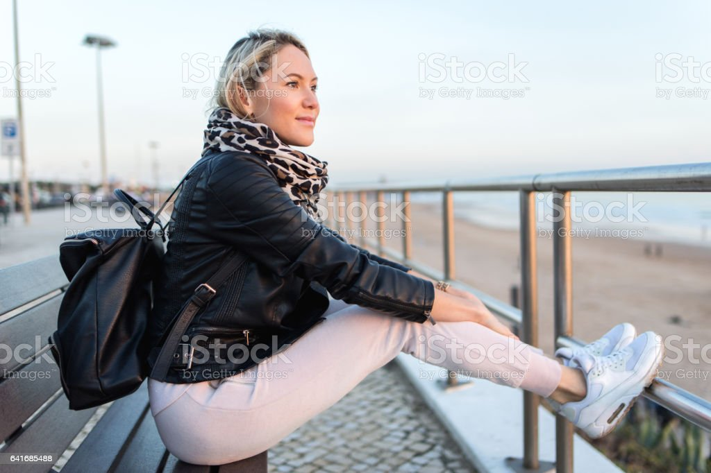 Beautiful young woman sitting on the coastline stock photo