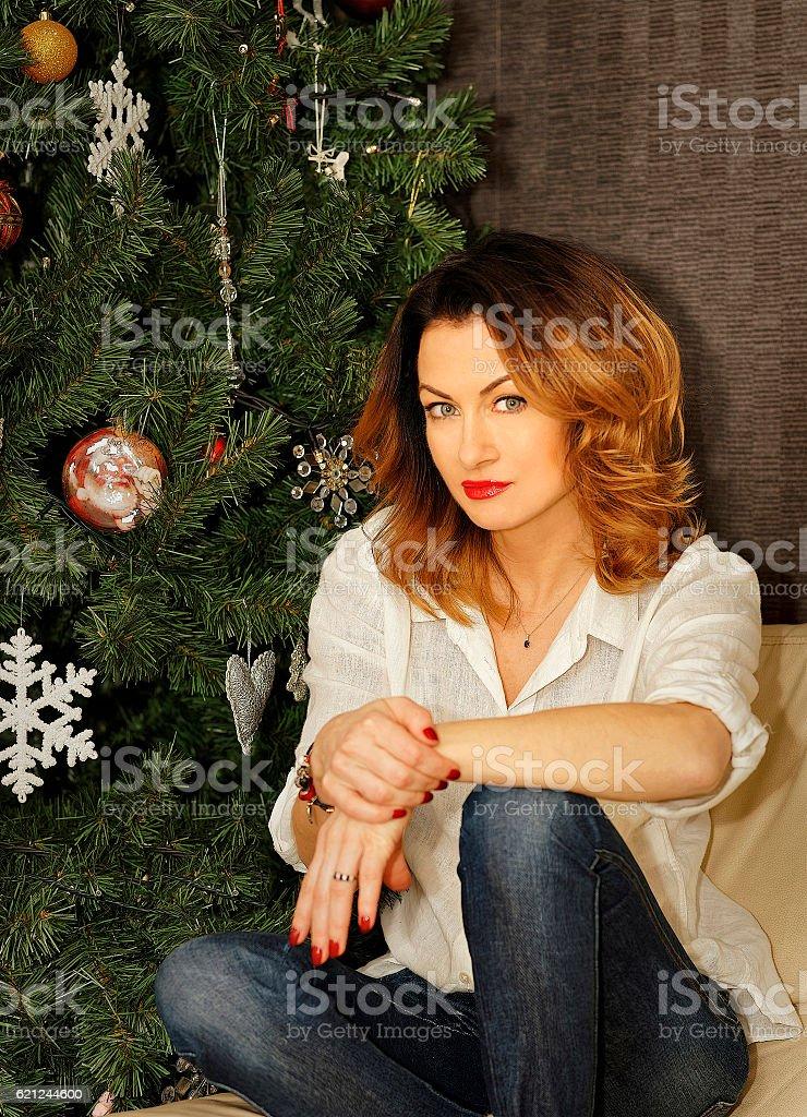 Beautiful young woman sitting on the sofa near Christmas tree stock photo