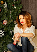 Beautiful young woman sitting on the sofa near Christmas tree