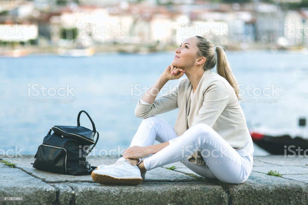 Beautiful young woman sitting on the street stock photo