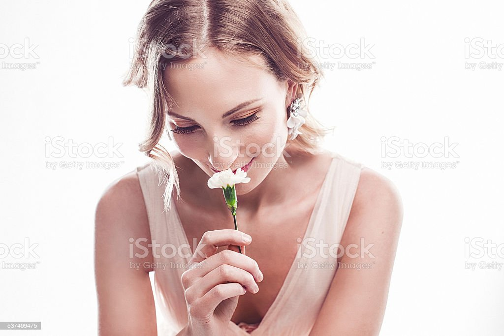 Beautiful young woman smelling a flower stock photo