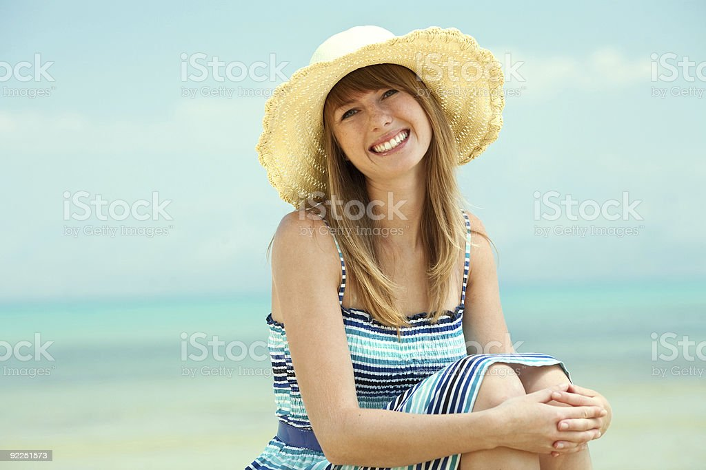 Beautiful young woman smiling on the beach stock photo