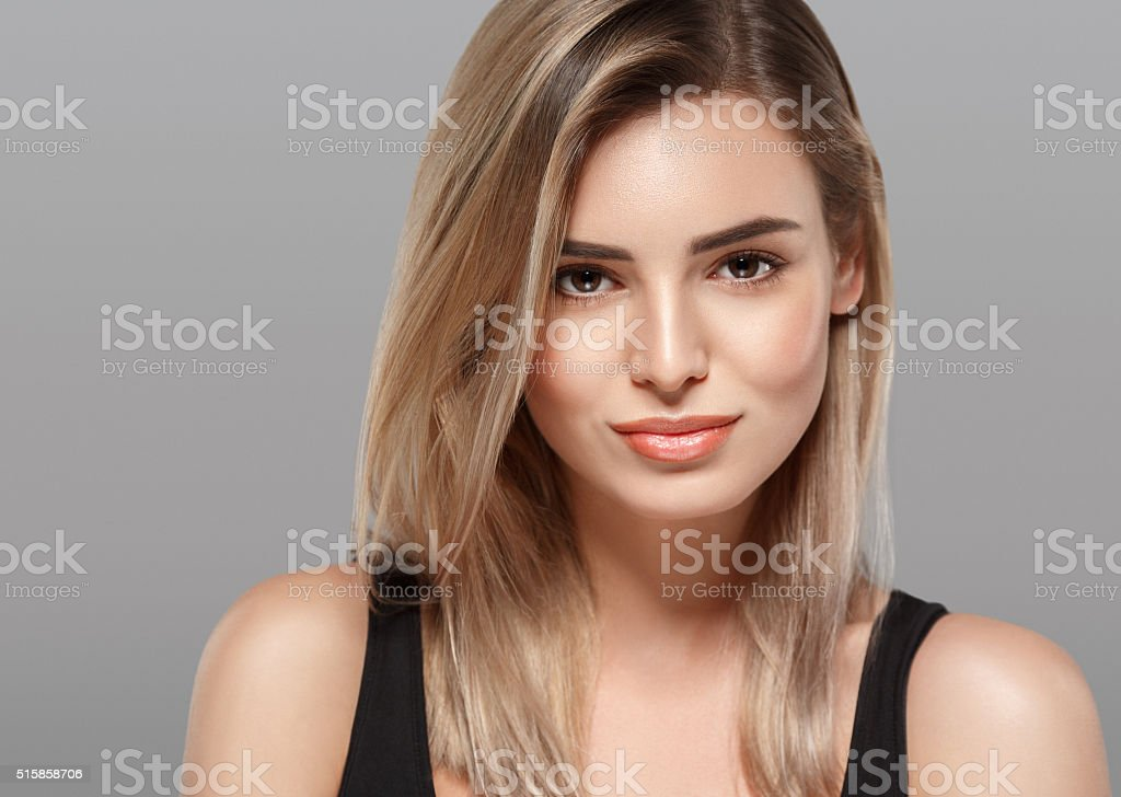 Beautiful young woman smiling posing on gray background stock photo