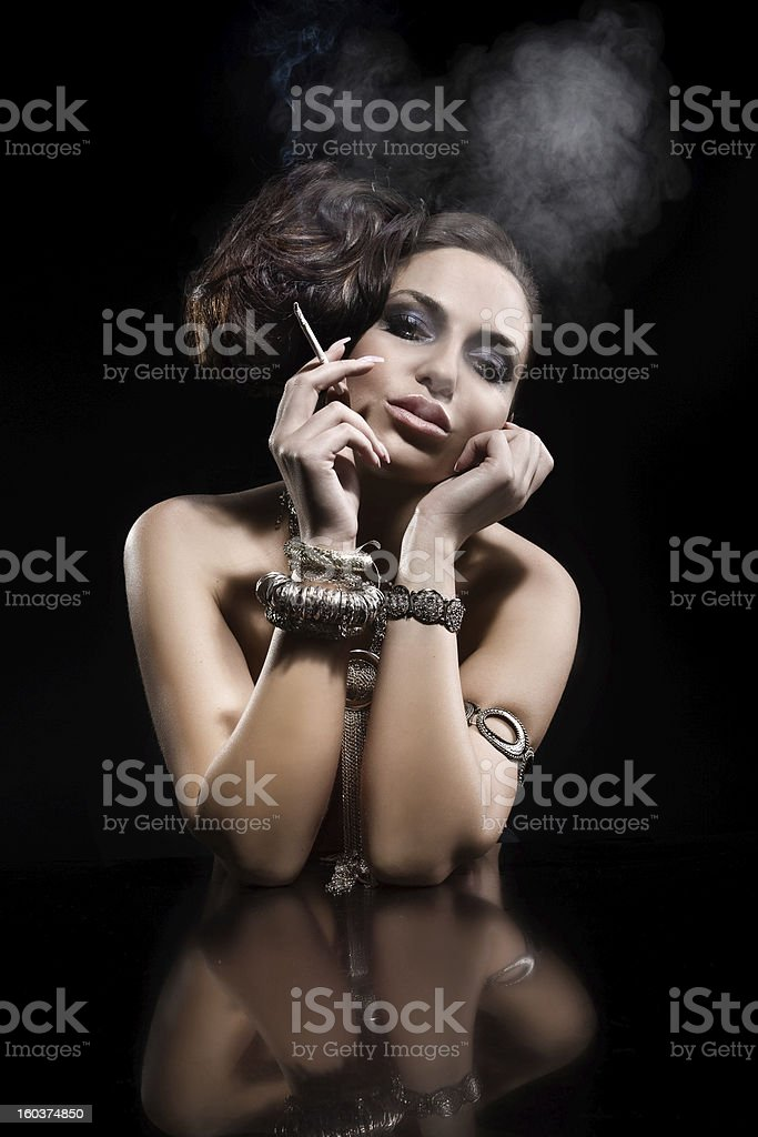 Beautiful young woman smoking a cigarette royalty-free stock photo