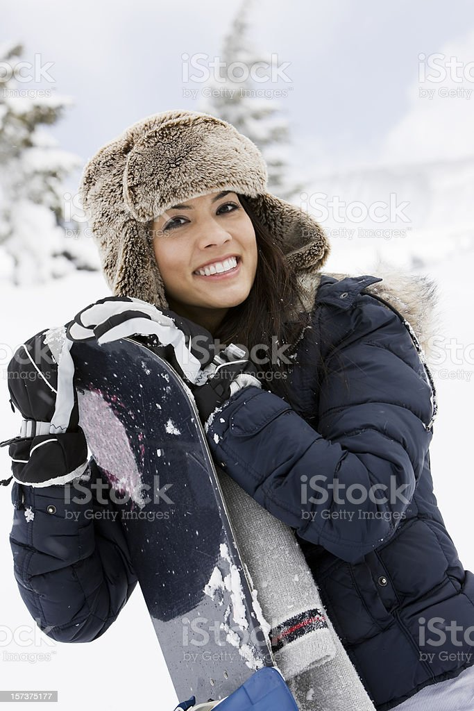 Beautiful Young Woman Snowboarder Smiling on Snowy Mountain royalty-free stock photo