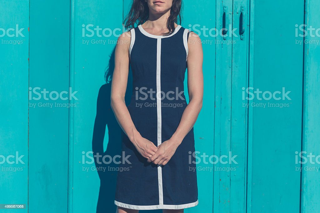 Beautiful young woman standing by blue door outside stock photo