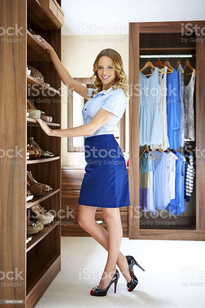 Beautiful young woman standing by her wardrobe smiling stock photo