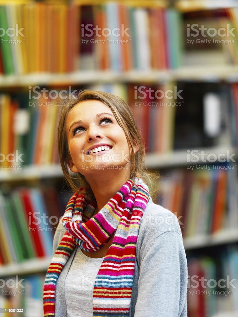 Beautiful young woman standing in library royalty-free stock photo