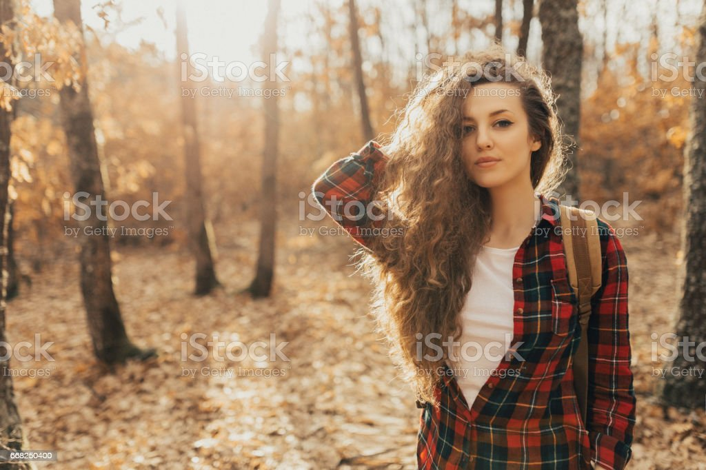 Beautiful young woman standing in the forest and looking at camera stock photo