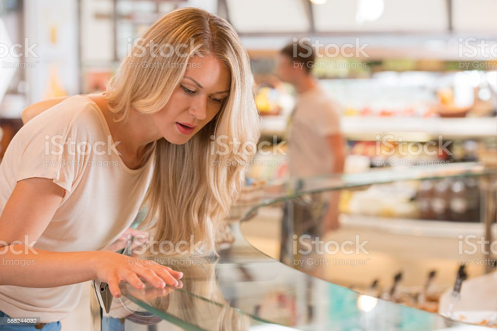 Beautiful young woman standing near supermarket showcase stock photo