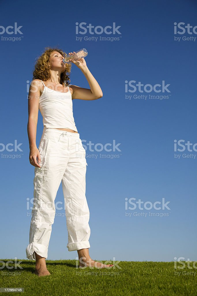 Beautiful young woman standing on grass and drinking water royalty-free stock photo