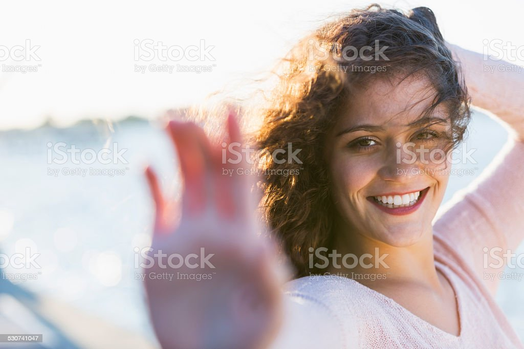Beautiful young woman standing outdoors by the water stock photo