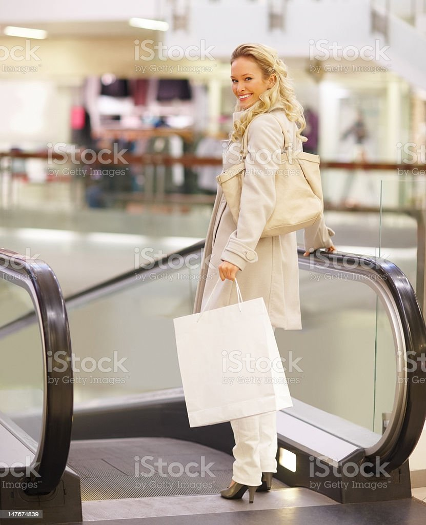 Beautiful young woman standing with shopping bags by escalator royalty-free stock photo