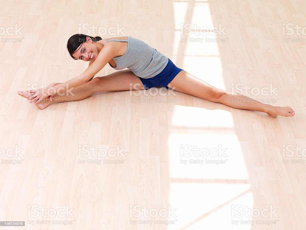 Beautiful young woman stretching legs on floor royalty-free stock photo