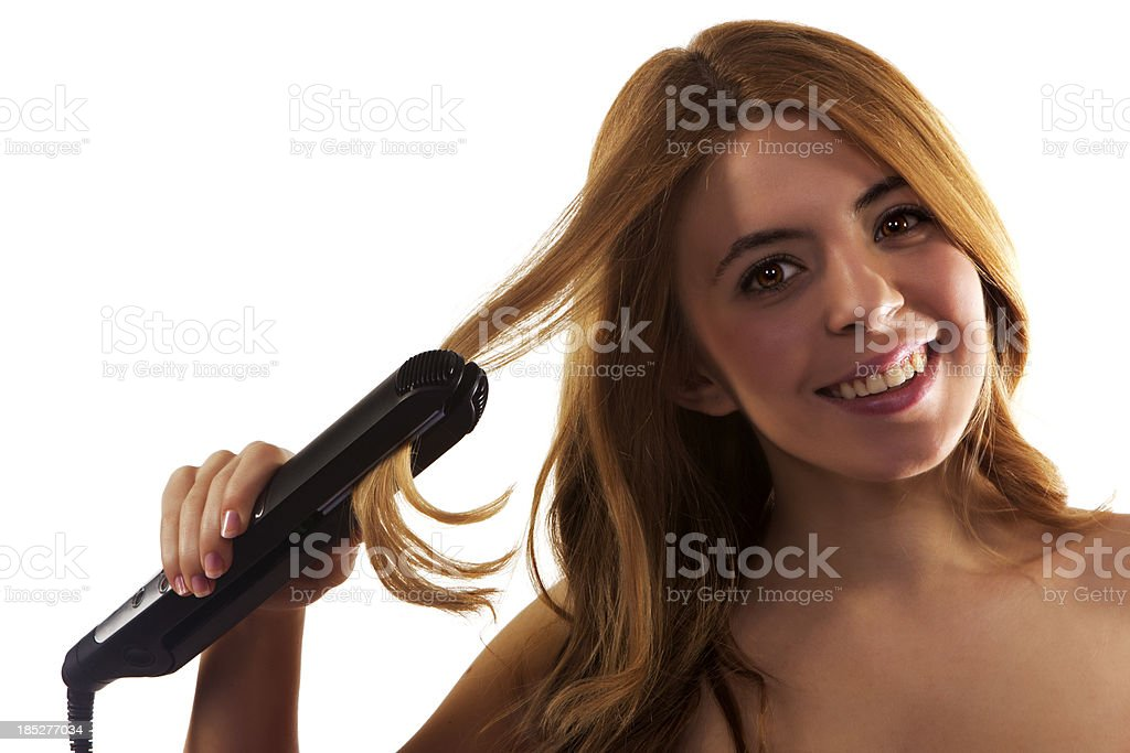 Beautiful young woman styling her hair with flat iron royalty-free stock photo