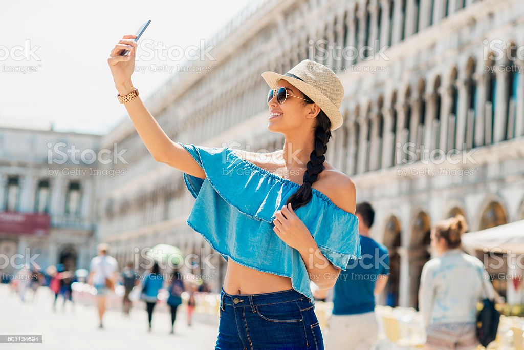 beautiful young woman taking a selfie on a town square stock photo