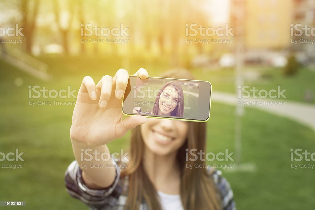 Beautiful young woman taking a selfie with phone stock photo