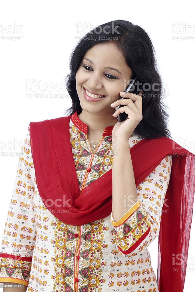 Beautiful young woman talking on mobile phone against white stock photo
