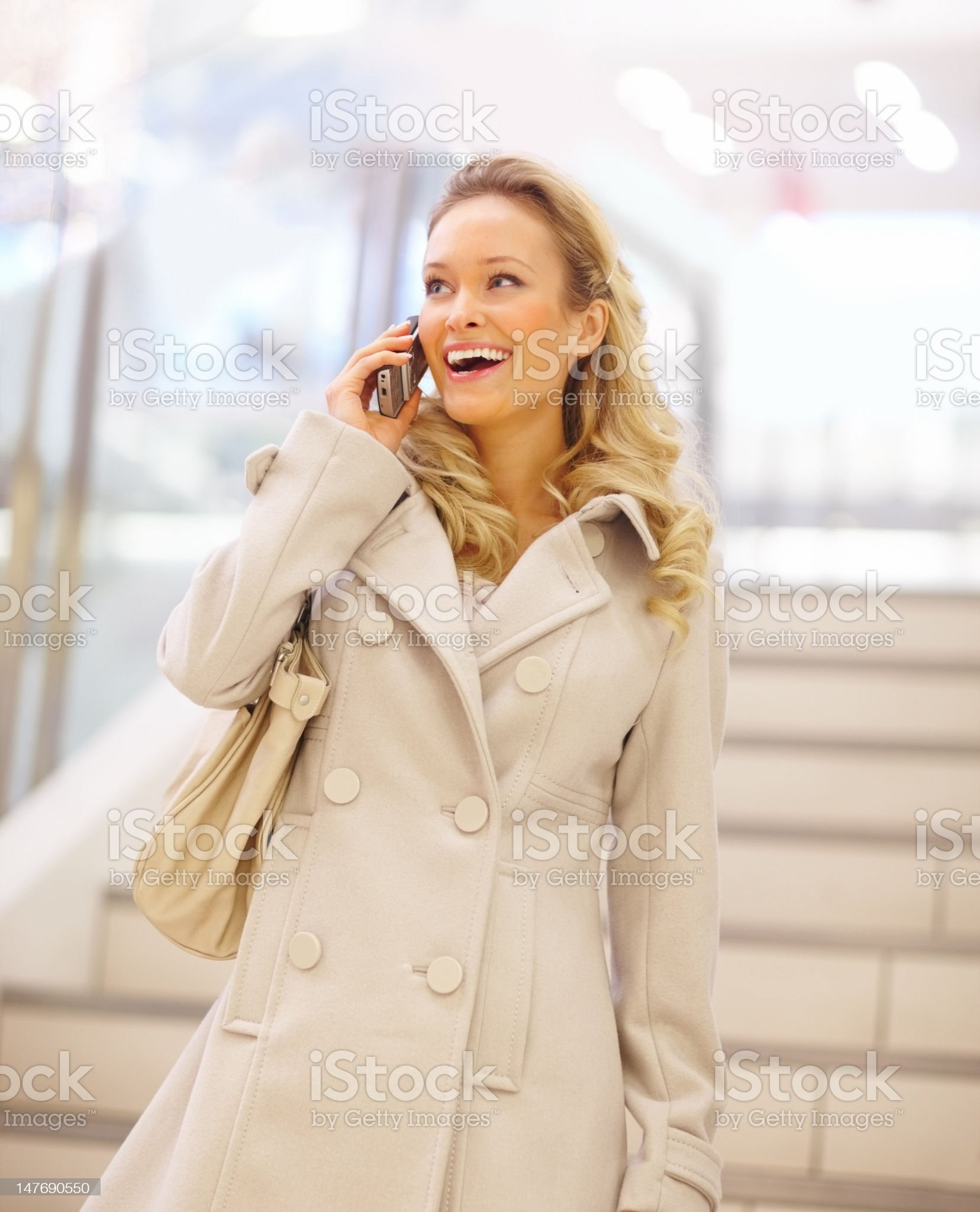 Beautiful young woman talking on mobile phone at shopping mall royalty-free stock photo