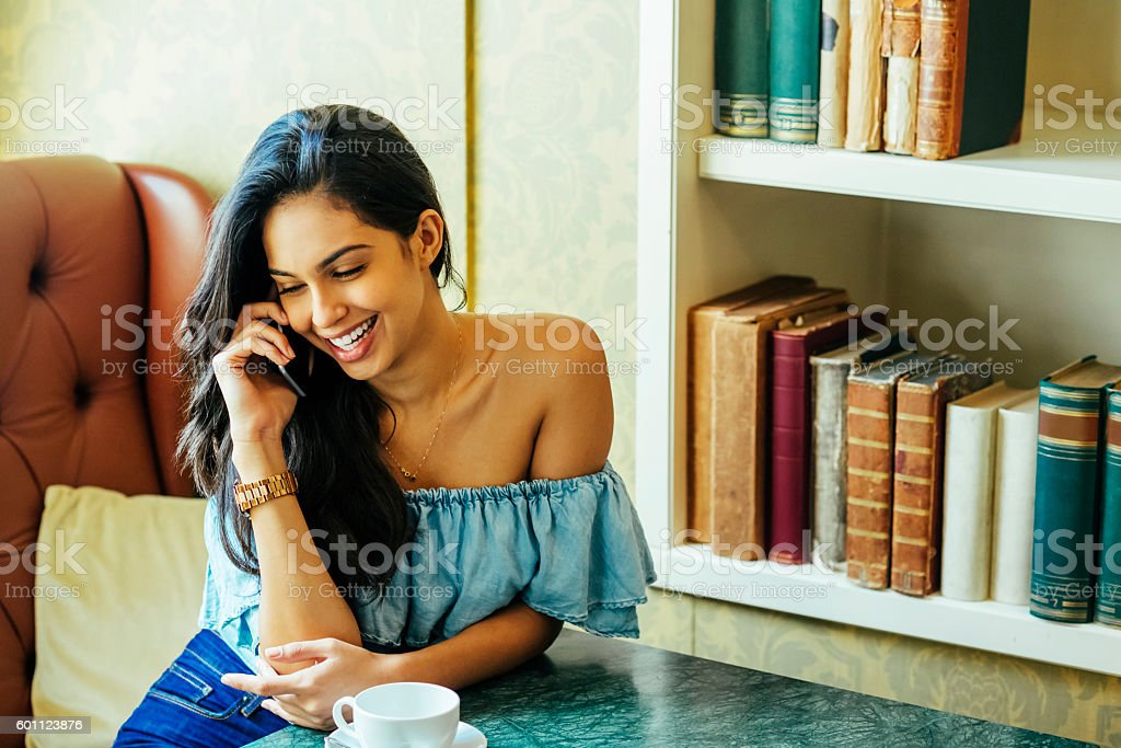 beautiful young woman talking on the phone in a bar stock photo