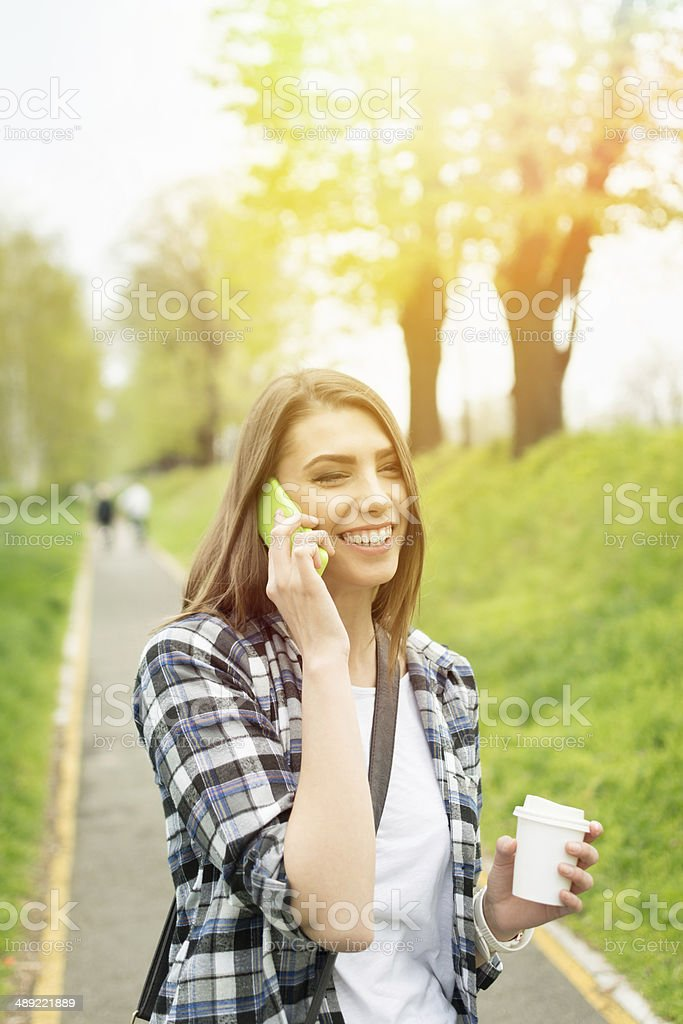 Cute happy Caucasian teenage girl talking on the phone holding cup of...