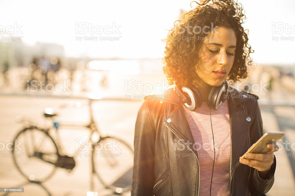Beautiful young woman texting on her smart phone. stock photo
