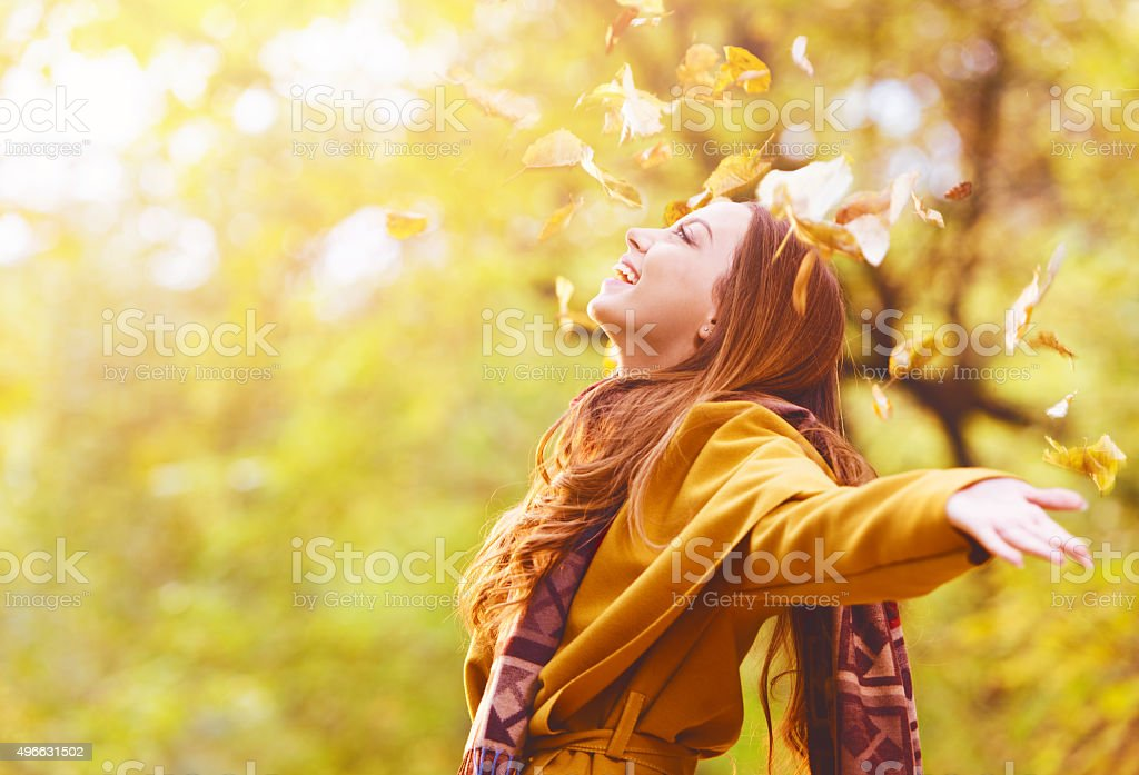 Beautiful young woman throwing leaves in a park stock photo